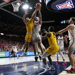 Arizona forward Ira Lee (11) and Cal's Matt Bradley (20) get tangled after reaching for a rebound during the Arizona-Cal game in McKale Center on February 21 in Tucson, Ariz.