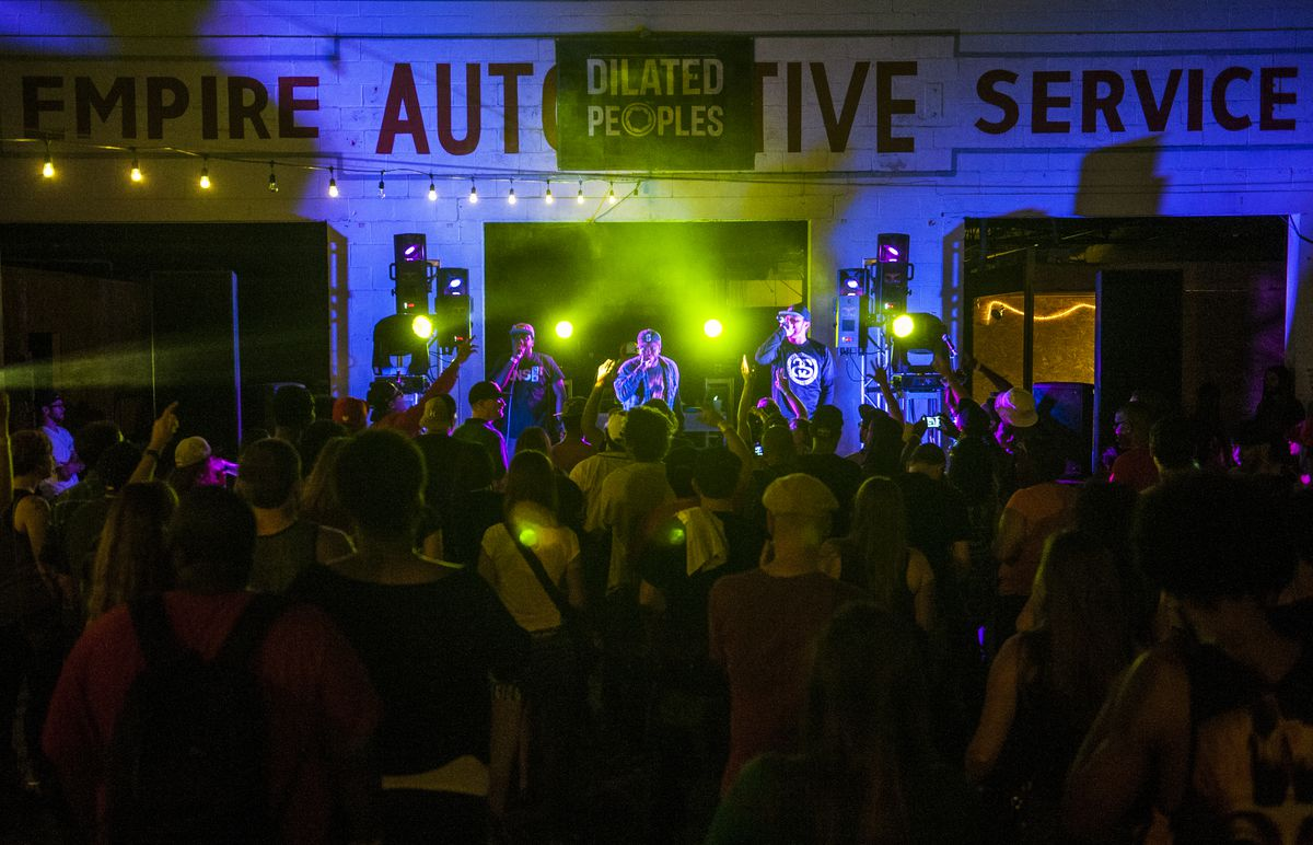 A crowd watching Austin-based hip-hop collective LNS Crew, performing in front of a wall that says Empire Automotive Service.