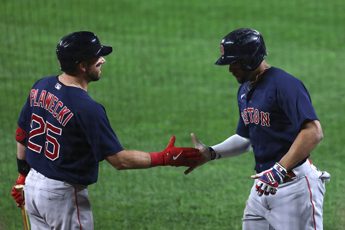 Xander Bogaerts #2 of the Boston Red Sox celebrates with Kevin Plawecki #25 after scoring in the sixth inning against the Baltimore Orioles at Oriole Park at Camden Yards on September 29, 2021 in Baltimore, Maryland.