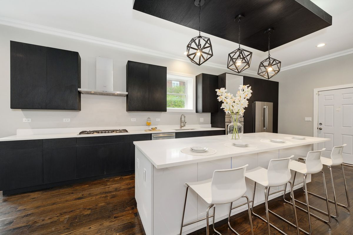 A large quartz island stands in the middle of a contemporary kitchen with dark wood cabinets and geometric pendant accent lights.