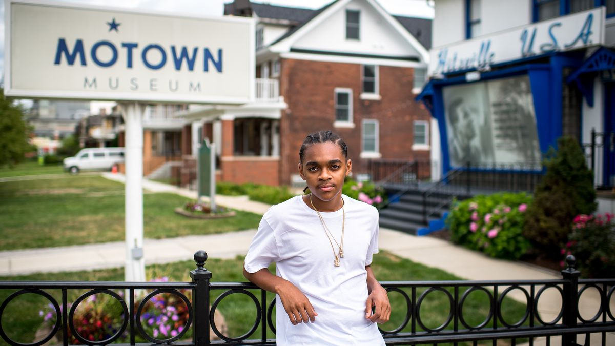 King Bethel, wearing a white shirt and gold necklaces, leans against a railing outside of Detroit's Motown Museum.