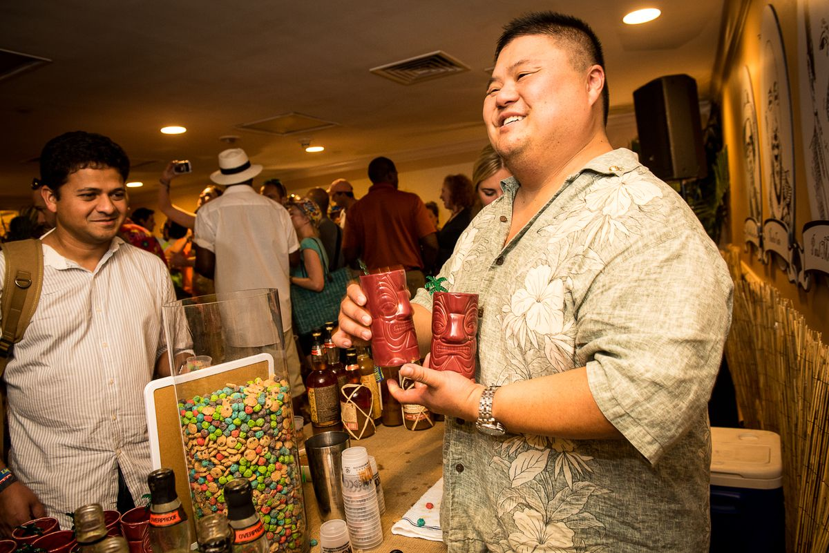 Rocky Yeh holding two tiki mugs while serving cocktails at an event.