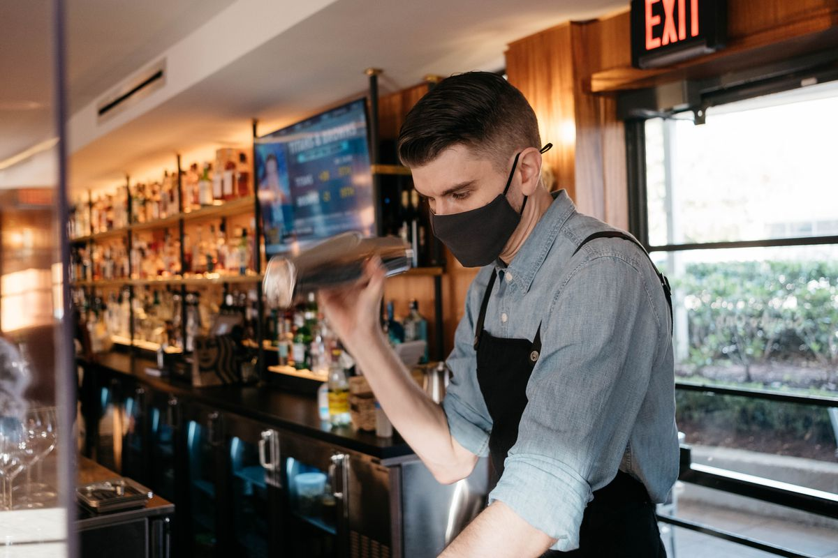 A bartender in a black mask, denim shirt, and black apron shakes a cocktail.
