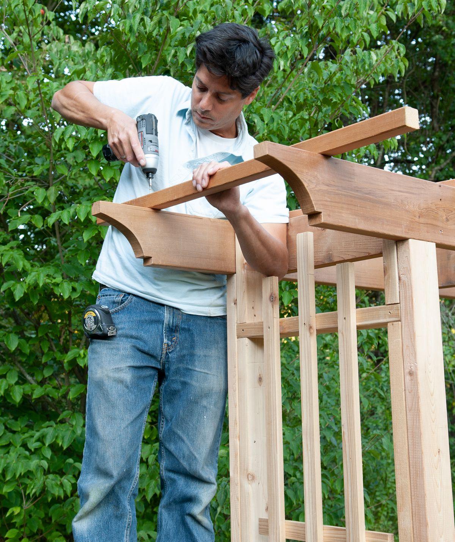 Man Installs Purlins Of Arbor Bench