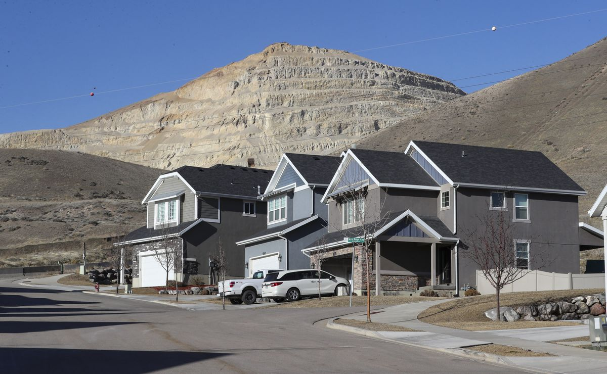 A huge rock cliff created byGeneva Rock's gravel operations looms in the background near a Lehi subdivision on Friday, Feb. 21, 2020.