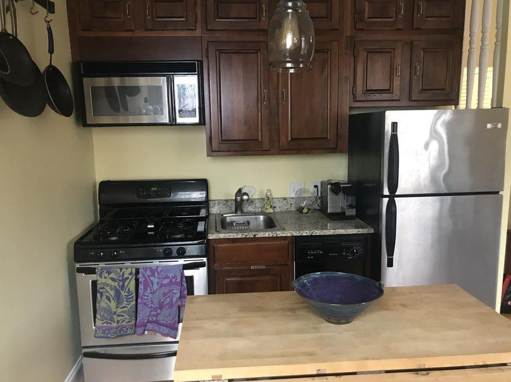 A small kitchen with a short row of countertop and fridge, as seen from over the kitchen's island.
