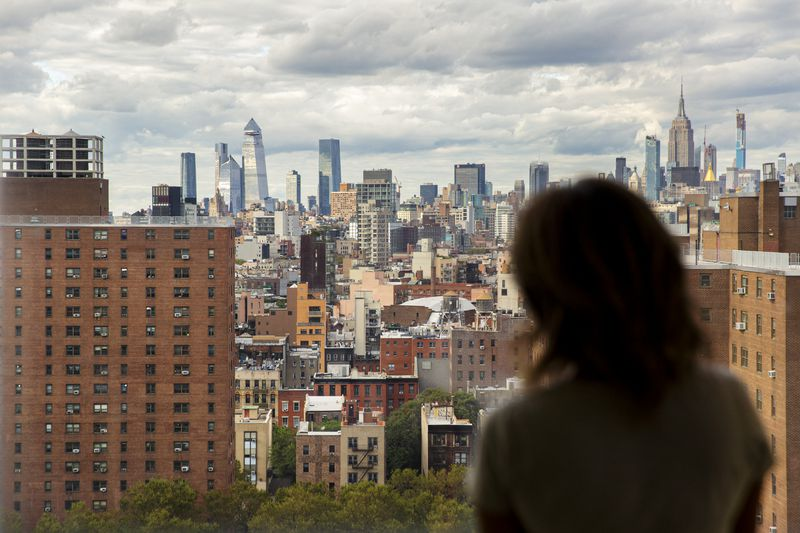 The New York City skyline as seen from the Lower East Side, with a woman's silhouette in the foreground.