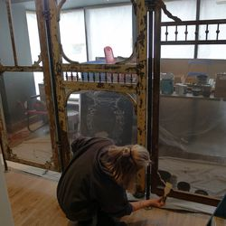 An artist works on a screen for the chef's table area made out of Victorian porch doors.