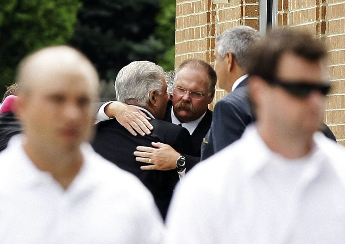 Philadelphia Eagles coach Andy Reid, center, is embraced after the funeral for his son Garrett Reid, Tuesday, Aug. 7, 2012, in Broomall, Pa.