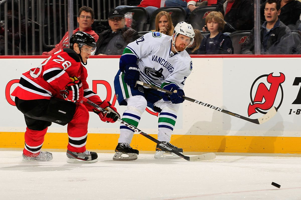 NEWARK, NJ - FEBRUARY 24: (R) Daniel Sedin #22 of the Vancouver Canucks fires a shot past (L) Anton Volchenkov #28 of the New Jersey Devils  at the Prudential Center on February 24, 2012 in Newark, New Jersey.  (Photo by Chris Trotman/Getty Images)