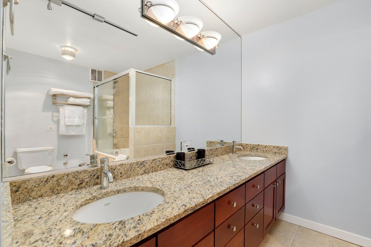 A bathroom with a stone counter with two sinks in front of a large mirror reflecting the glass shower enclosure and toilet.