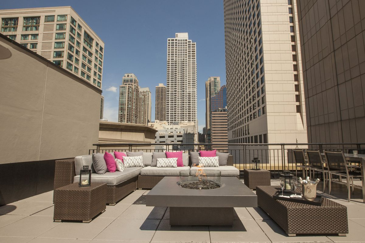 A rooftop lounge on top of a hotel, the Chicago skyline is in the background