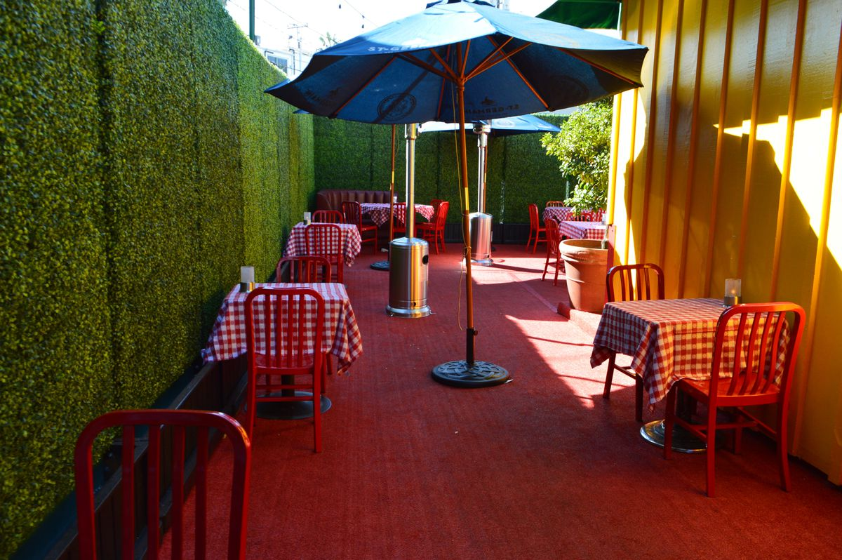 Outdoor dining area at Dan Tana's with red checkered tablecloths, umbrella, and faux greenery on walls.