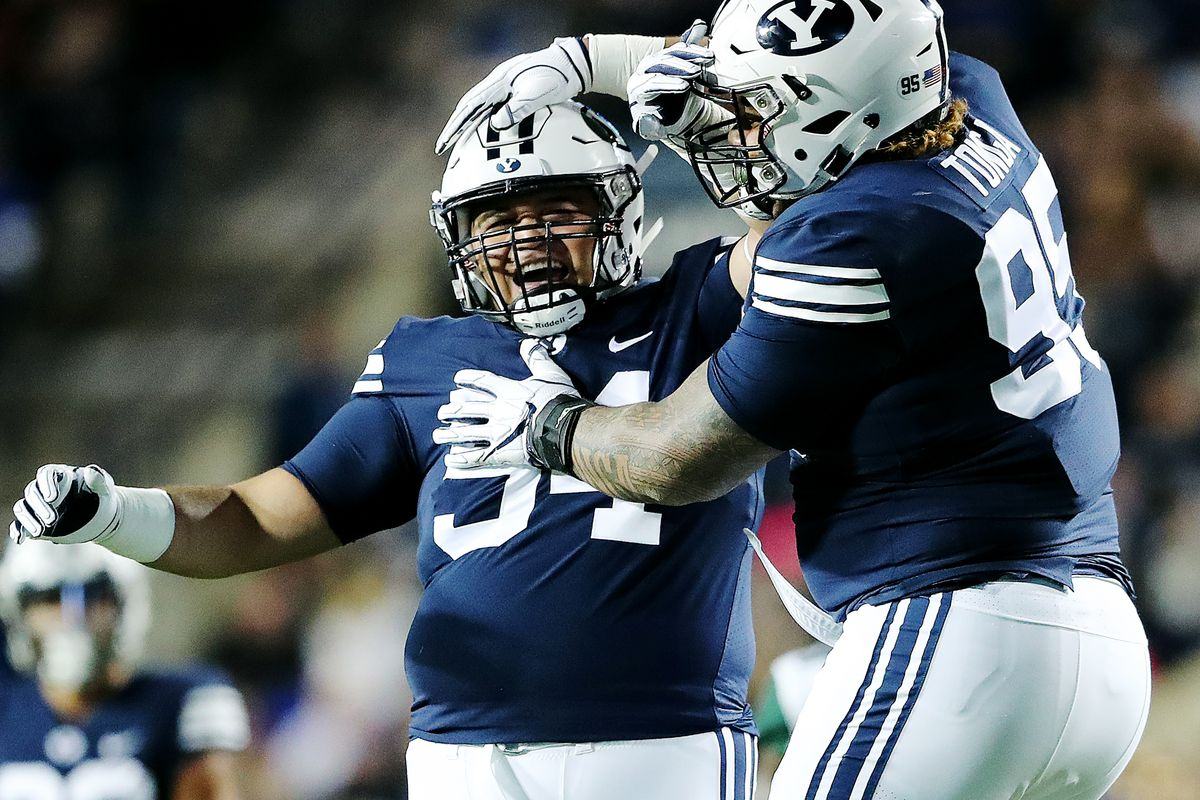 Brigham Young Cougars defensive lineman Khyiris Tonga (95) celebrates a sack on Hawaii Warriors quarterback Cole McDonald (13) with teammate Brigham Young Cougars defensive lineman Kamalani Kaluhiokalani (94) as BYU and Hawaii play at LaVell Edwards Stadium in Provo on Saturday, Oct. 13, 2018.