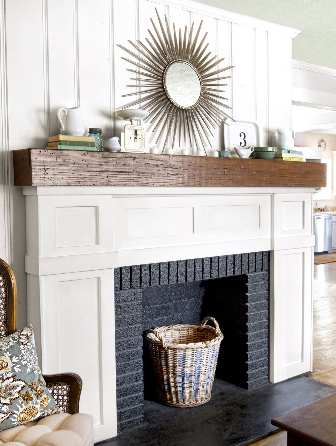 <p>After: White wood trim brightens the fireplace, which is accented by a rustic mantelshelf; a black-painted firebox adds depth.</p>