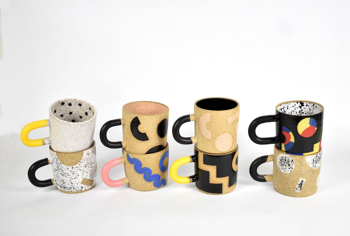 Four patterned ceramic mugs are stacked on top of four additional ceramic mugs, with different patterns and colors
