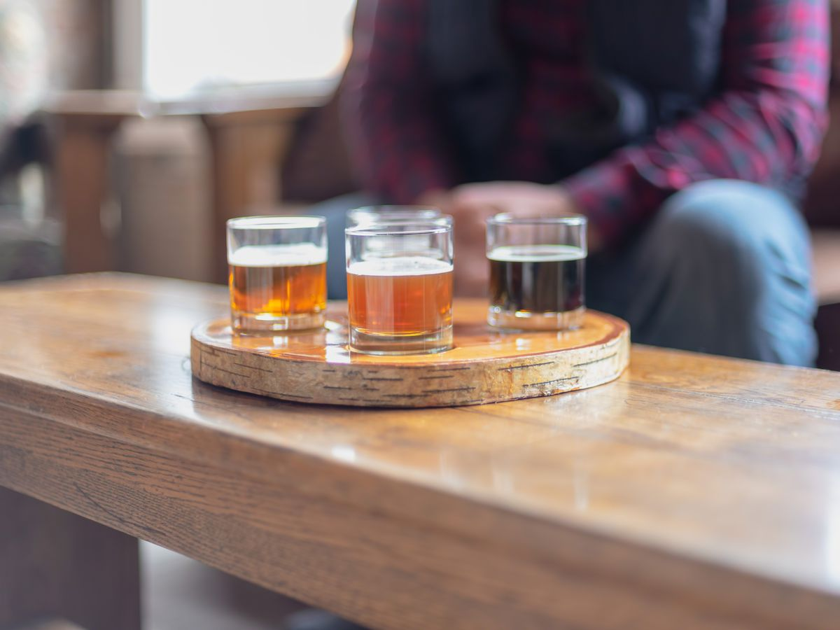 A beer flight in a round wooden carrier on a table.