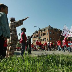 Residents of a west side Chicago neighborhood watch public school teachers march after a rally Saturday, Sept. 15, 2012 in Chicago.