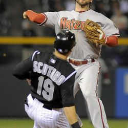 Colorado Rockies' Marco Scutaro (19) is forced out at second by Arizona Diamondbacks second baseman Ryan Roberts, top, during the fourth inning of a baseball game on Friday, April 13, 2012, in Denver.