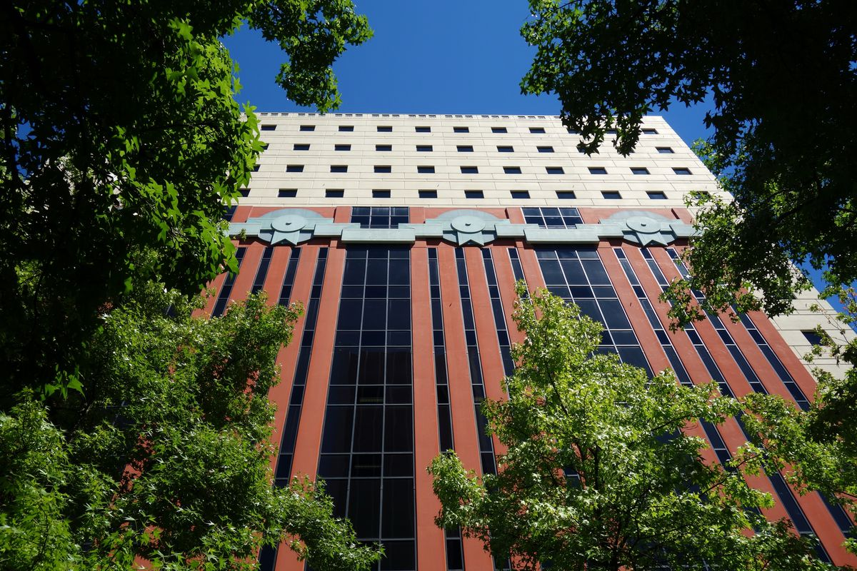 The exterior of a postmodern Portland building. The facade is red and white. There are trees in the foreground.