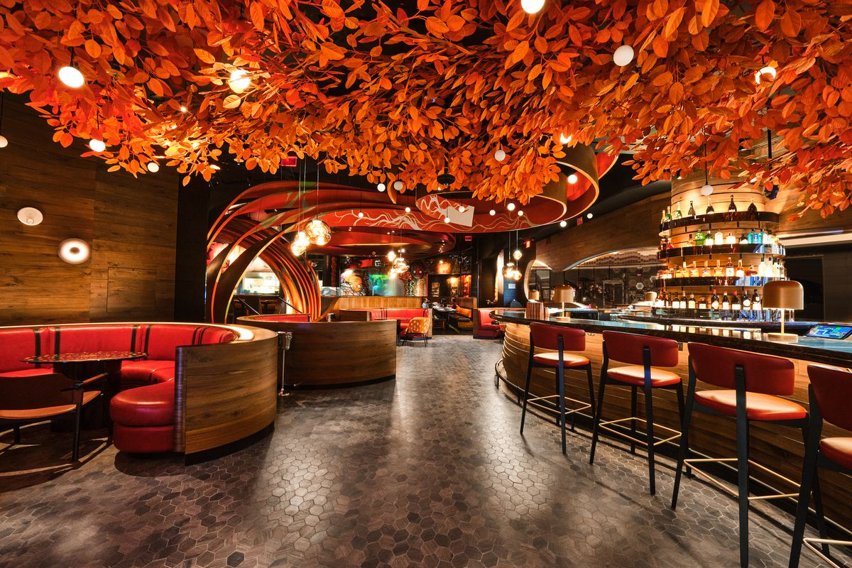 A lounge with a bar to the right and booths to the left with a canopy of orange leaves overhead.