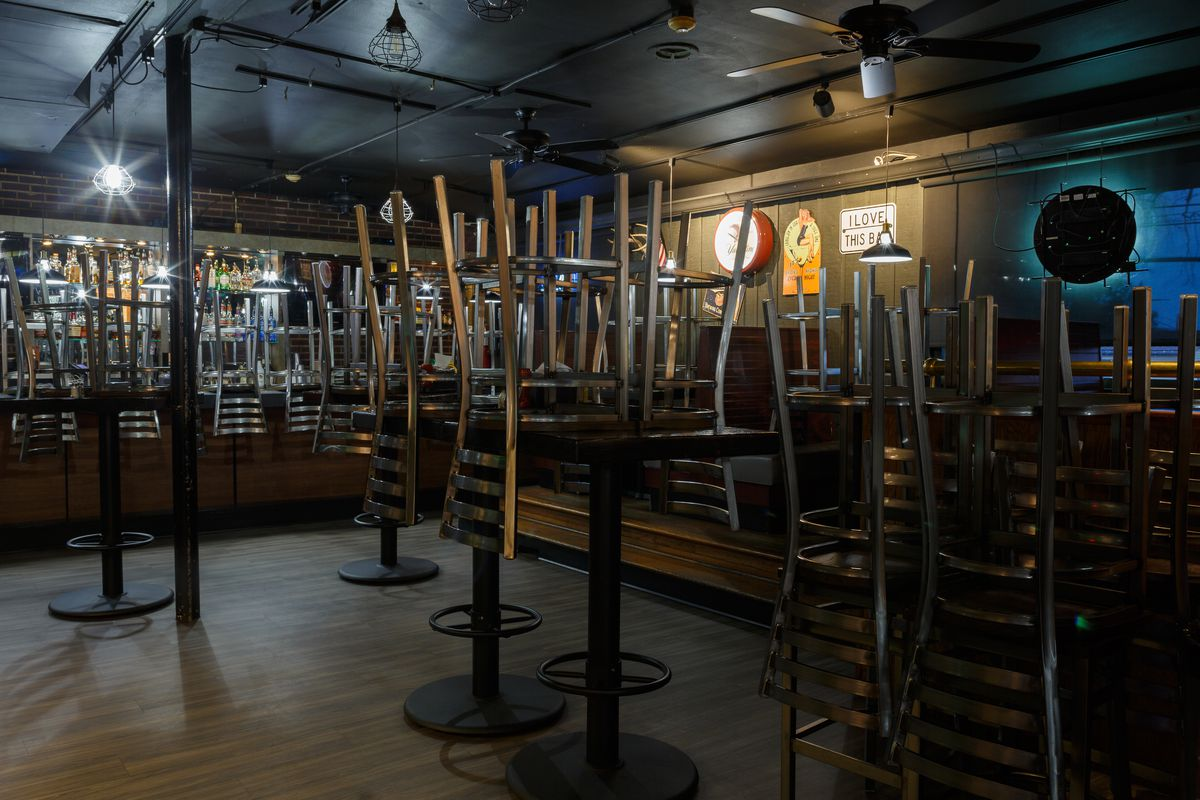 Empty restaurant/bar with all the chairs stacked on the tables.