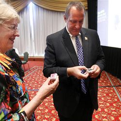 Utah Attorney General Mark Shurtleff (right) and Joyce Bennett, wife of Senator Bob Bennett, look at the small Amber Alert tracking device at the Marriott in downtown Salt Lake City Monday.