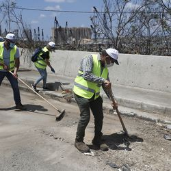 Volunteers who traveled from the Bekaa valley in Eastern Lebanon to help clean the city, damaged homes and give other assistance, clean a street near the site of last week's explosion, in Beirut, Lebanon, Tuesday, Aug. 11, 2020. The explosion that tore through Beirut left around a quarter of a million people with homes unfit to live in. In the absence of the state residents of Beirut opened their homes to relatives, friends and neighbors. And on the streets, it was young volunteers with brooms, not government workers, who swept the streets littered with shattered glass.