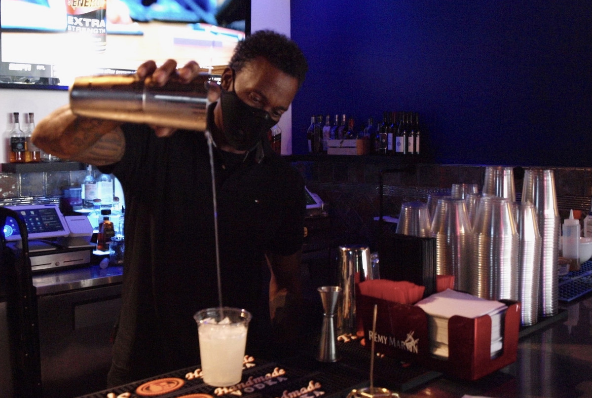 A bartender pours a drink from a metal shaker into a plastic cup.
