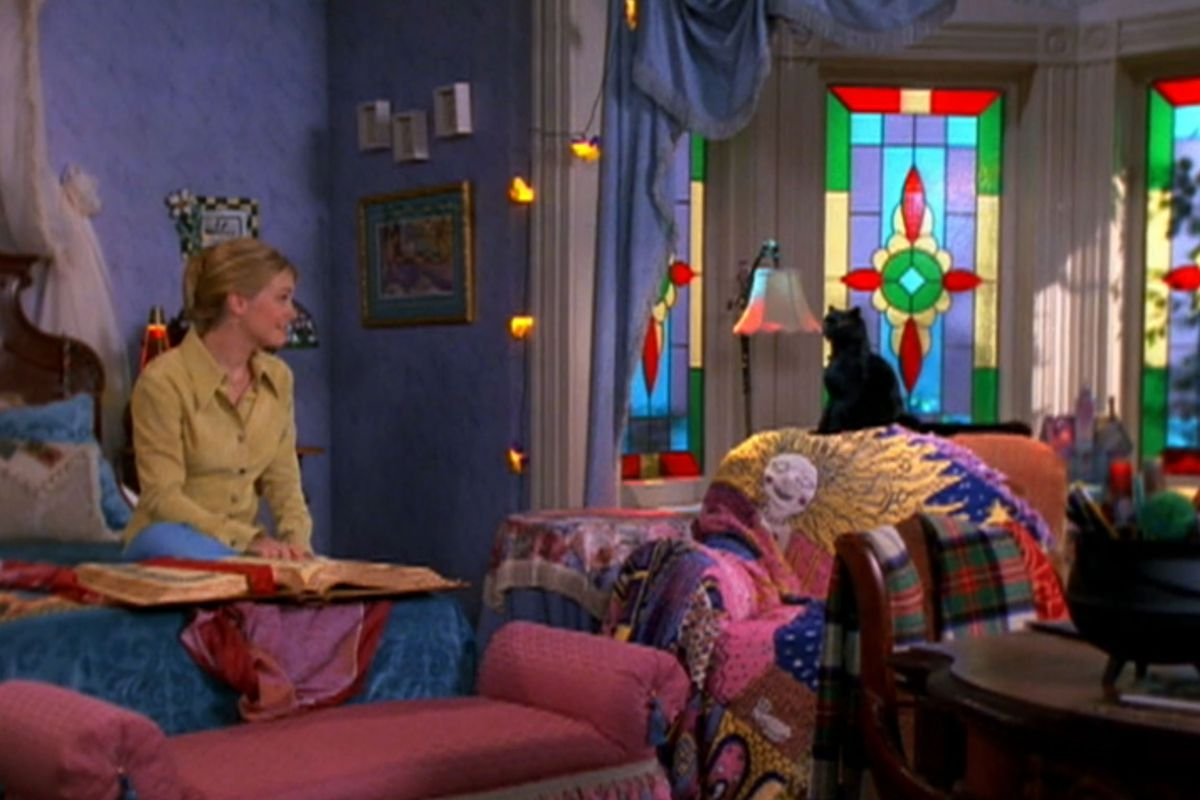 A bedroom. The walls are painted purple and the windows are made of colorful stained glass. There is a bed with blue bed linens and a red bedroom bench. An armchair holds various assorted linens and items. There are hanging string lights.