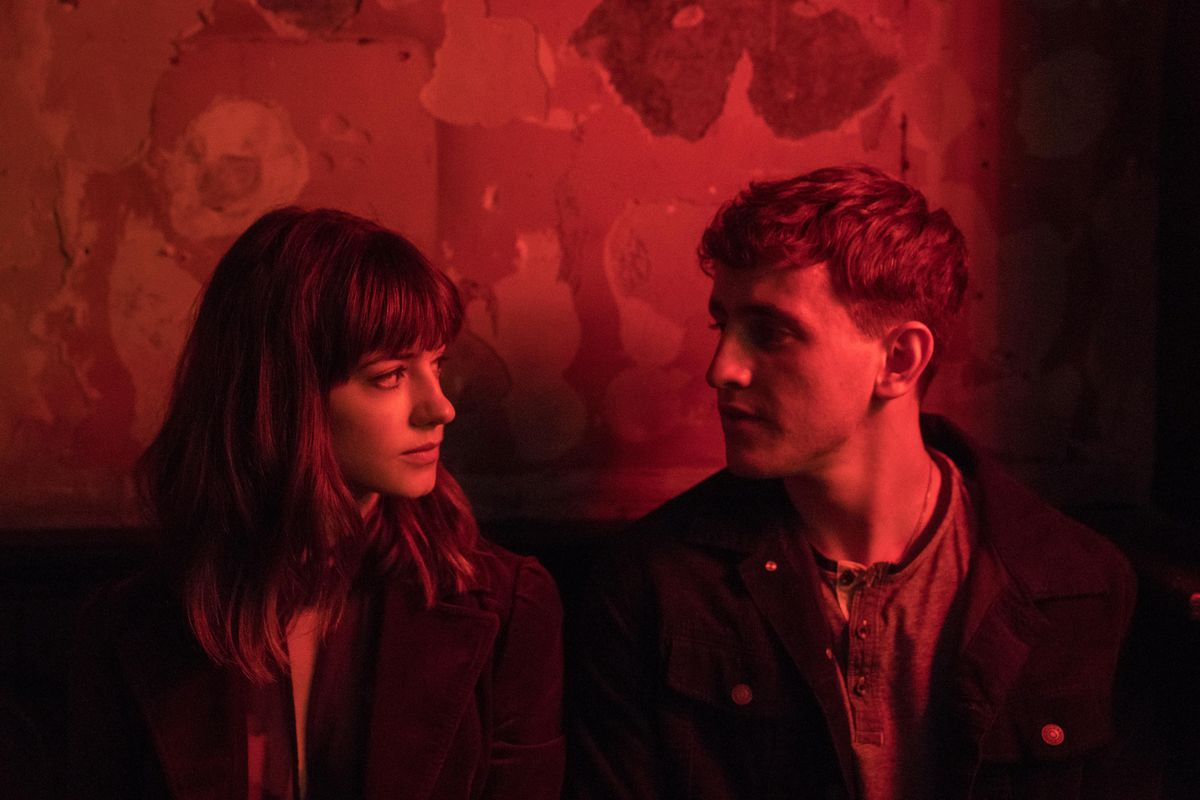 A young man and woman sit next to each other, gazing at each other, under red lighting.