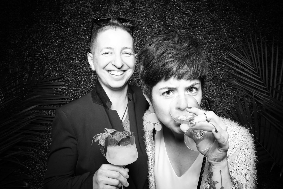 A black and white photograph of two women drinking and smiling