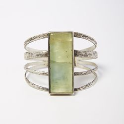 """<span class=""""credit"""">Sterling silver and prehnite cuff, <a href=""""http://personastyle.com/collections/joseph-gordon-cleveland/products/sterling-silver-and-prehnite-cuff-by-joseph-gordon-cleveland"""">$6485</a></span><p>"""