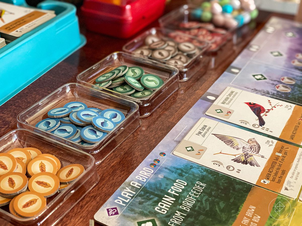 A selection of tokens in plastic trays, with cards filled with bird art along the sideboard.