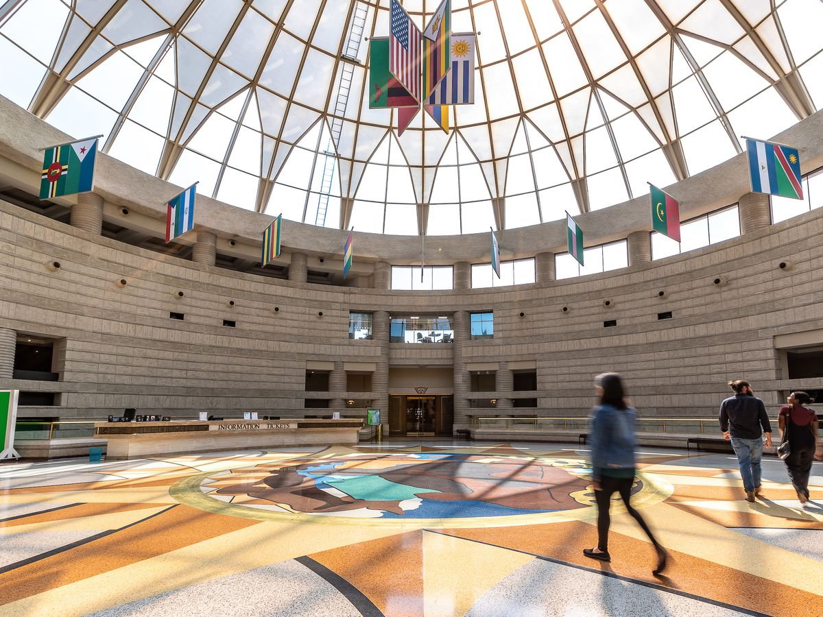 The interior of the Charles H. Wright Museum of African American History. The floor is painted with a colorful pattern. The ceiling is a dome shape and is glass. There are various flags hanging from the ceiling and attached to the wall.