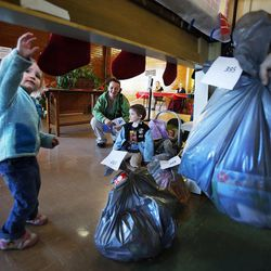 Danielle Andrus, center, and her son Zech watch as bags of gifts are brought through the chimney for them during the 2014 Operation Chimney Drop at Head Start in Salt Lake City, Monday, Dec. 15, 2014. At left is Danielle's daughter Charity.