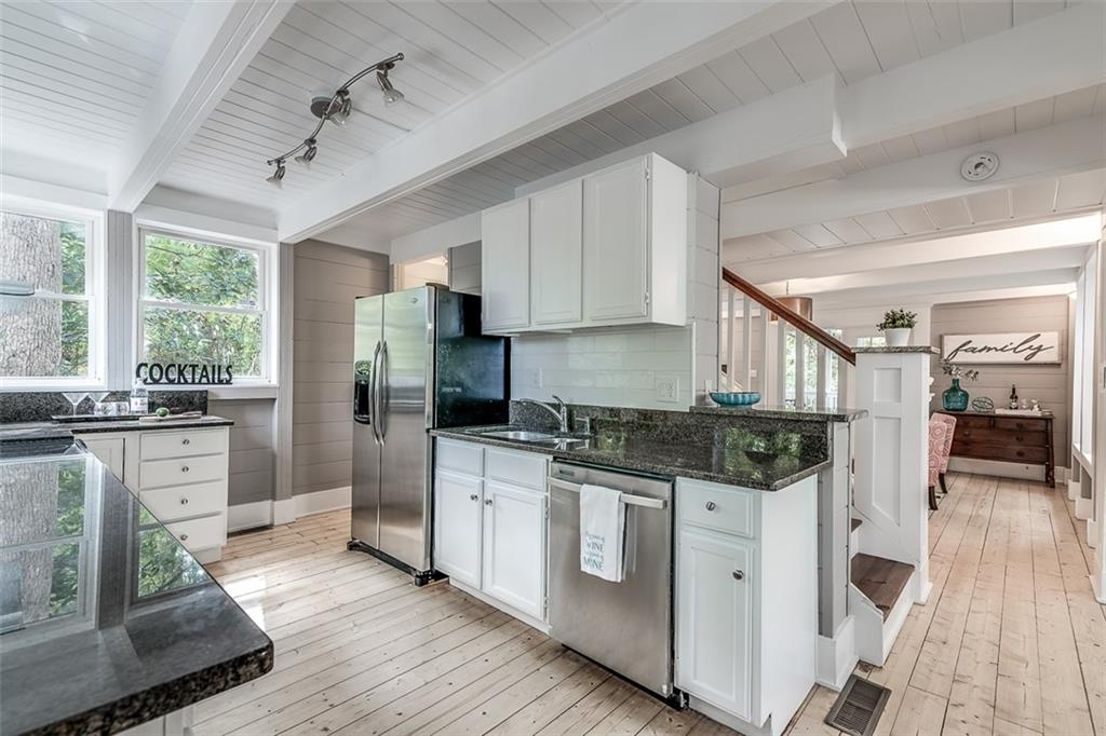 A kitchen with wood floors and ceiling and black counters.