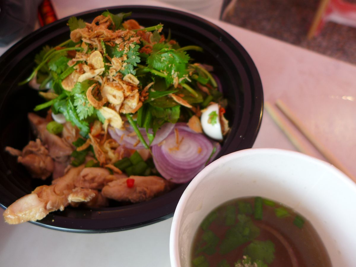 A bowl of chicken and herbs with broth on the side.