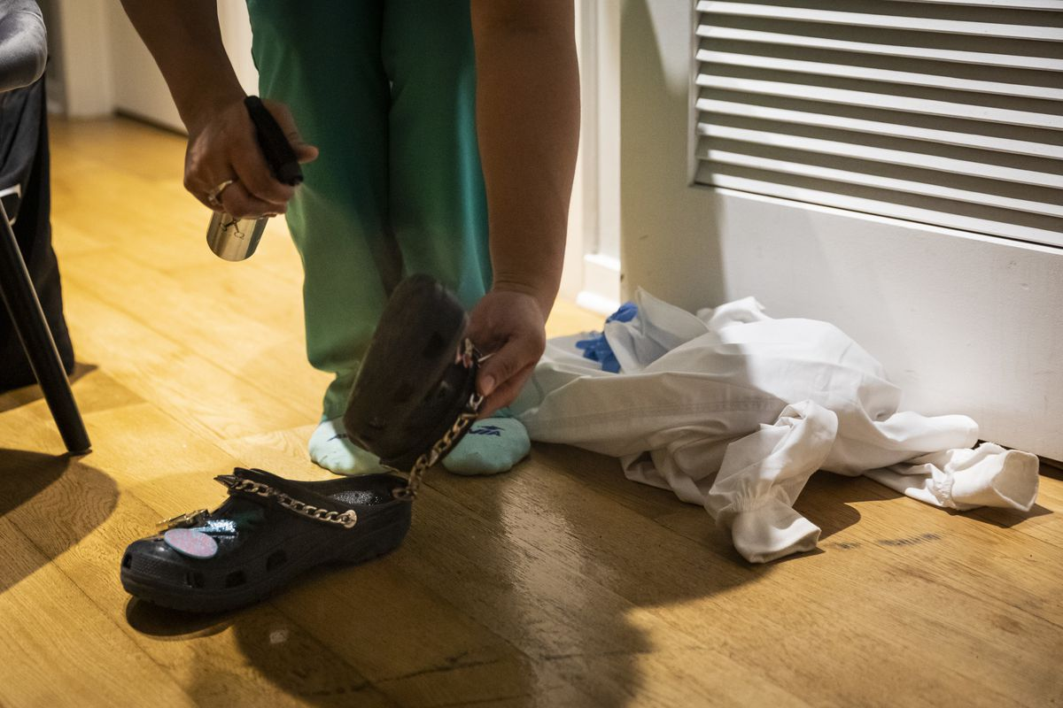 Nurse practitioner Capri Reese sprays her Crocs with antibacterial spray, then puts her scrubs in the washing machine and immediately showers at her South Loop apartment after a 12-hour shift at Roseland Community Hospital, where three patients suffering from COVID-19 died, Tuesday afternoon, April 28, 2020.