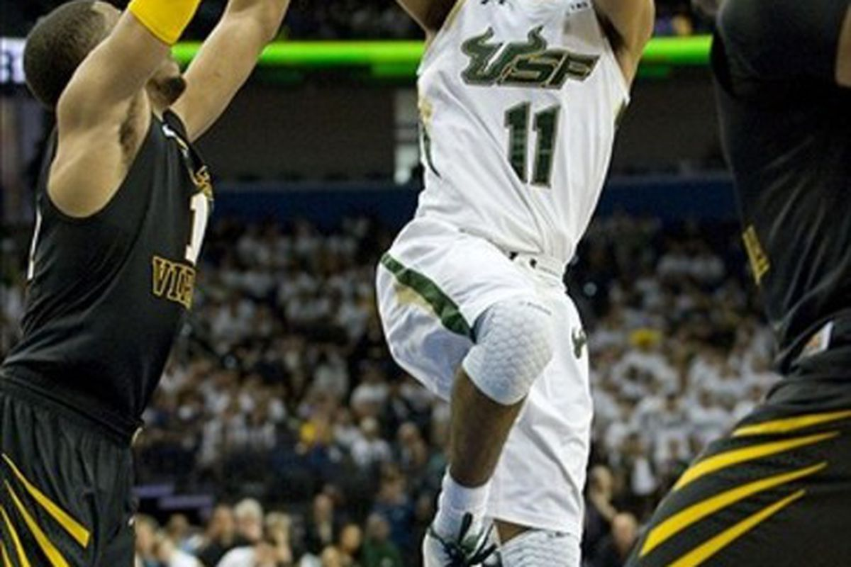 March 3, 2012; Tampa, FL, USA; South Florida Bulls guard Anthony Collins (11) shoots over West Virginia Mountaineers forward Dominique Rutledge (1) at the Tampa Bay Times Forum.  Mandatory Credit: Jeff Griffith-US PRESSWIRE