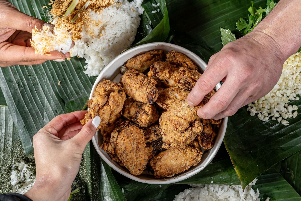 Hands dig into a bucket of fried chicken, surrounded by rice piled on green banana leaves