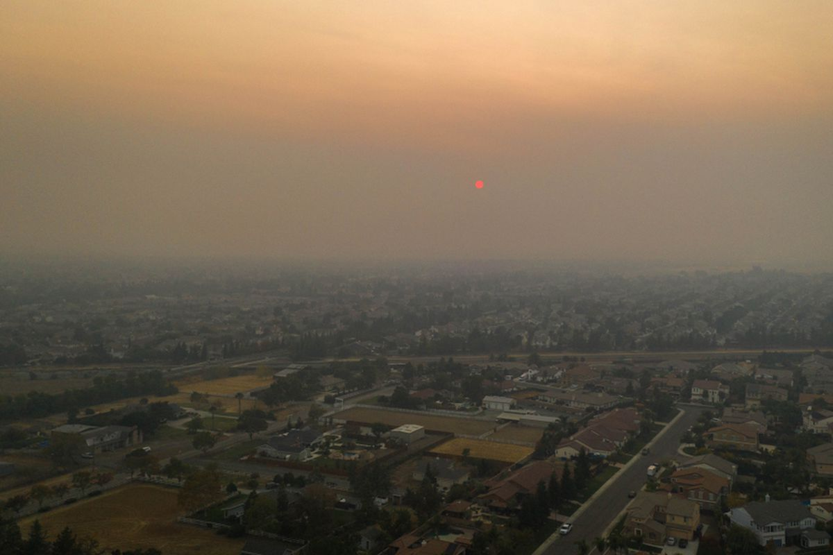 Smoke settling over a town in Butte County, seen from the air.