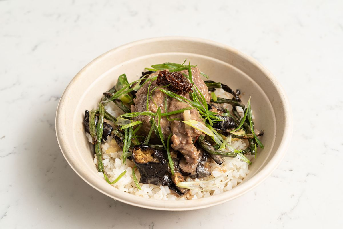 A heaping bowl of Filipino kare kare on marble for takeout.