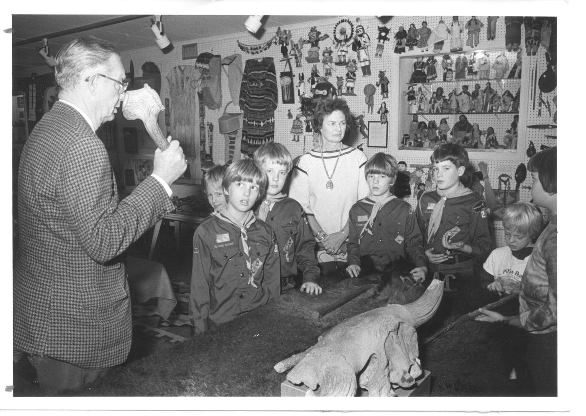 """John and Betty Mitchell shared their collection and knowledge of Native-American artifacts with a boy scout troop in the basement of John's real estate office the """"Green Bay Trading Post Museum,"""" on Green Bay Road in Evanston, c. 1970. 