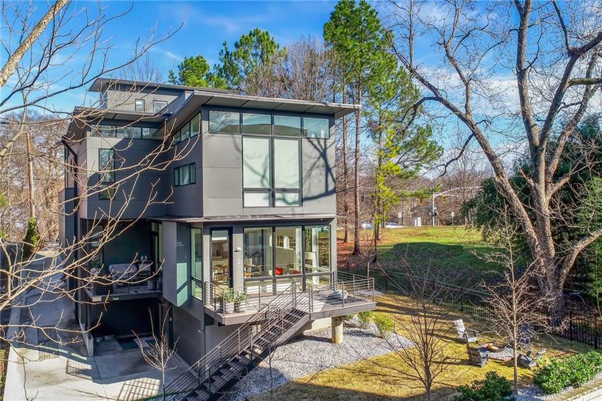 A large gray modern house with a rooftop deck and frontyard fire pit.