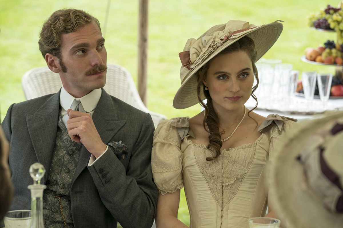 A man in a nice suit and a lady in an old dress and hat at a garden party in A Fortunate Man