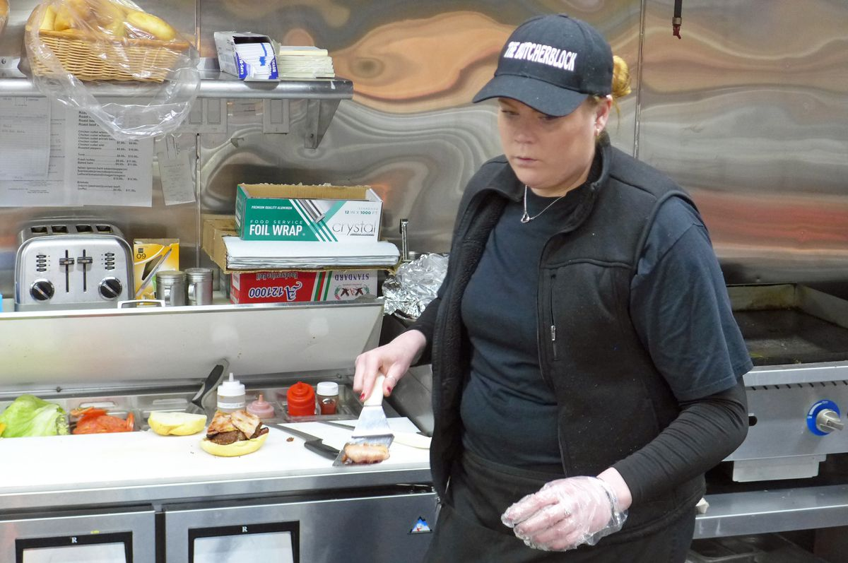A woman in a black outfit prepares a sandwich, turning away from the counter momentarily toward the viewer.