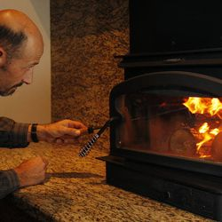 Timothy Olschewski stokes a fire in his Lennox Perform C210 Phase II EPA-certified wood-burning stove in his home in West Valley City Thursday, Jan. 8, 2015. The stove has a two-tier burning system that emits cleaner fumes.