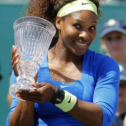 Serena Williams celebrates with the championship trophy after defeating Lucie Safarova, of the Czech Republic, during their finals match at the Family Circle Cup tennis tournament in Charleston, S.C., Sunday, April 8, 2012. Williams won 6-0, 6-1.