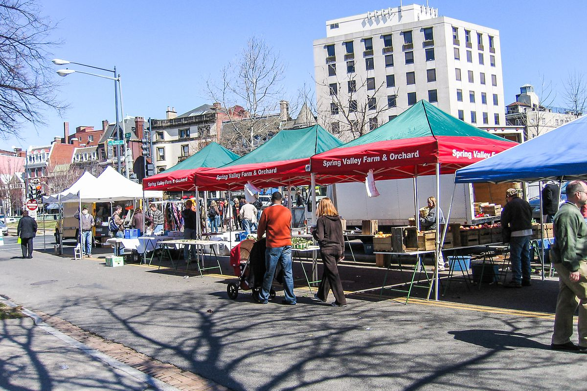 A couple, a man and a woman, walk with a baby in a stroller through the Dupont Circle farmers market on 20th Street NW. Several vendors under pop-up canopies line the street.